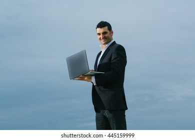 handsome male businessman with smiling face in black formal jacket and white shirt working on laptop outdoor on cloudy sky background