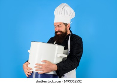Handsome male chef with saucepan. Chef man in hat holds pan. Man in chef uniform with saucepan. Bearded man cook in kitchen. Healthy food cooking. Chef cooking tasty dish in kitchen. Kitchen utensils.