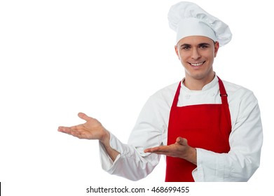 Handsome male chef in uniform showing something and smiling.