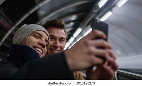 Handsome male couple take a photo together  on a subway escalator