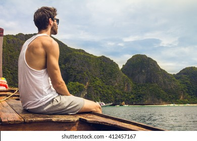 Handsome male cruising on retro wood boat by Andaman sea and behind him you can see Ko Phi Phi Lee Island in full glory. He's turned his back and enjoying the view.