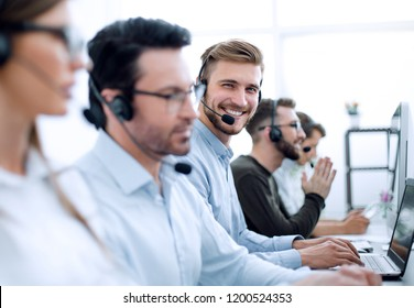 handsome male customer support phone operator with headset working in call center