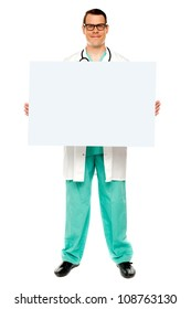 Handsome male doctor displaying white advertising board, full length shot