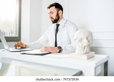 Handsome male doctor in the medical gown working with laptop sitting in the beautiful white office interior