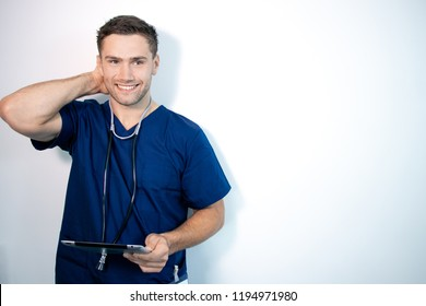 Handsome male doctor or nurse in blue scrubs, holding digital tablet and smiling while looking at camera