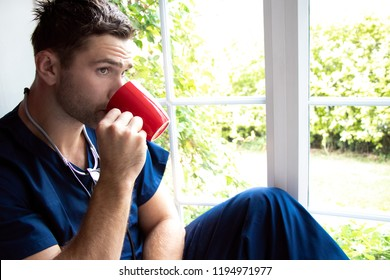 Handsome male doctor or nurse on break wearing blue scrubs drinking from cup and looking out of window