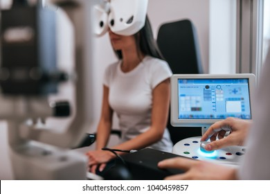 Handsome male doctor  ophthalmologist is checking the eye vision of attractive young woman in modern clinic. Doctor and patient in ophthalmology clinic.