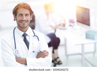 Handsome male doctor smiling with arms crossed on chest portrait