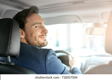 Handsome male driver in car