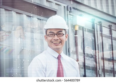 Handsome male engineer is smiling for work. The man is a white helmet is looking at the screen with aspiration.