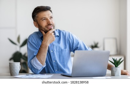 Handsome Male Entrepreneur Sitting At Workplace With Thoughtful Face Expression, Having Inspiration, Pensive Businessman Thinking About Business Strategy, Touching Chin And Smiling, Free space