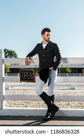 handsome male equestrian leaning on fence and holding open sign at horse club
