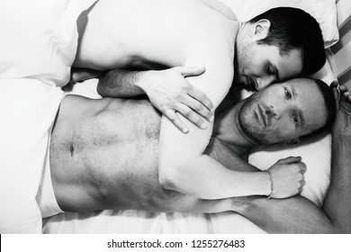 Handsome male gay couple lying together in bed, one kissing other looking at camera