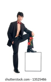 Handsome male gigolo with flower, foot on advertising board,  Studio shot, white background