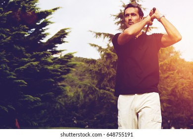 Handsome male golfer following through from a swing during professional game. Mature man practicing his swing on the golf course