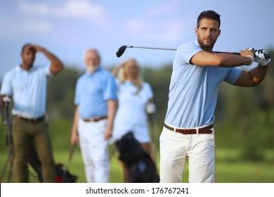 Handsome male golfer swinging golf club, following shot in the air.