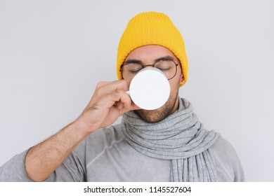 Handsome male having sore throat influenza. Portrait of sick man have virus and drinking cup of tea, wearing glasses, yellow hat, grey sweater and scarf. People, health, medicine