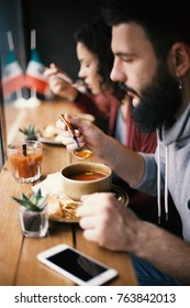 A handsome male hipster with a beard eating a hot soup at a cafe, lunch break.