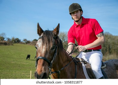 Handsome Male Horse Rider on horseback with white breeches, black boots and red polo shirt in green field with horses in background.