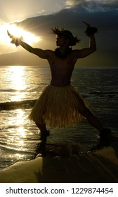 Handsome male hula dancer performing a traditional dance as the sun sets over the ocean.
