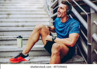 Handsome male jogger listening to music while taking break after morning training in urban setting