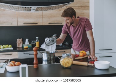 Handsome male looking at the dish in the saucepan