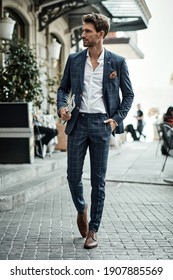 Handsome male model in checked suit walking on the street with newspaper