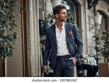 Handsome male model in checked suit walking on the street - Shutterstock ID 1907885587