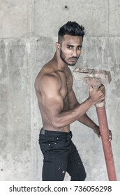 Handsome male model with a muscled gym fit body and a stylish modern haircut is posing shirtless in front of a grey concrete wall