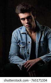 Handsome male model posing in fashion blue jeans jacket looking on dark shadow background. Closeup portrait