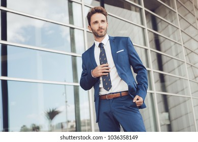 Handsome male model posing wearing a blue suit.