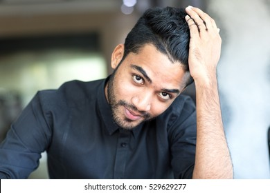 Handsome male model striking his hair in thoughts while looking in the camera