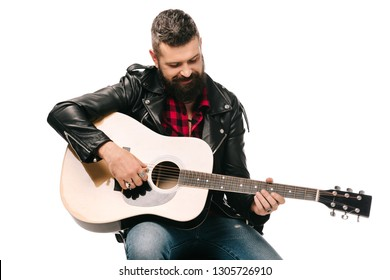 handsome male musician in black leather jacket playing on acoustic guitar, isolated on white