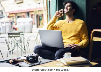 Handsome male owner of marketing company resting while having mobile conversation with  friend postpone supervising task sitting with equipment in comfortable coworking space using wifi connection