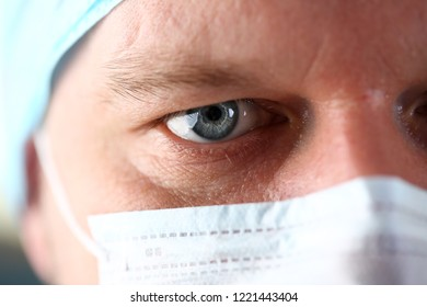 Handsome male physician face wearing protective mask closeup.