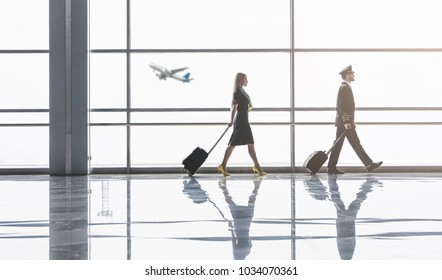 Handsome male pilot and attractive female flight attendant are walking in airport terminal together in front of panoramic wondows.
