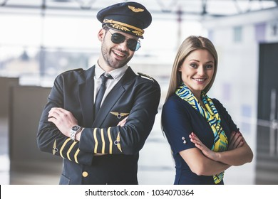 Handsome male pilot and attractive female flight attendant are standing in airport terminal together.