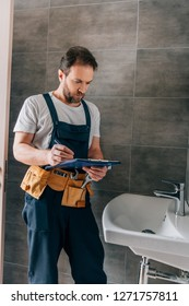handsome male plumber with toolbelt writing in clipboard near broken sink in bathroom