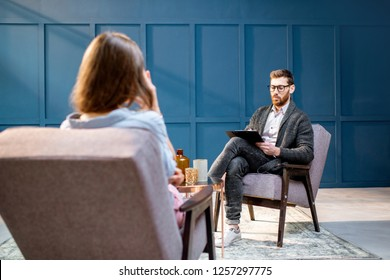 Handsome male psychologist listening to the woman client sitting during psychological session in the blue office interior