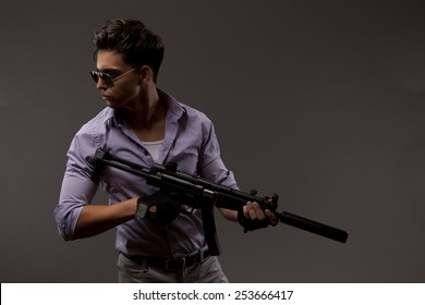 Handsome male shooter or contractor with automatic rifle