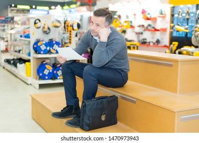 handsome male shopkeeper keeping accountancy books