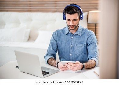 Handsome male is sitting in bedroom at table with laptop while wearing earphones and using touchpad