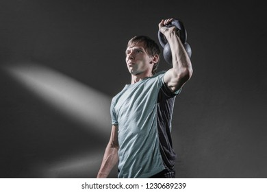 Handsome male in sportswear lifting heavy kettlebell with one arm and looking away while exercising on gray background