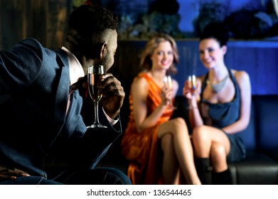 Handsome male staring at attractive young girls in night club.
