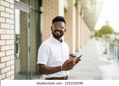 Handsome male student with eyeglasses talking with friends on mobile phone enjoying urban coffee while walking on street after productive day.