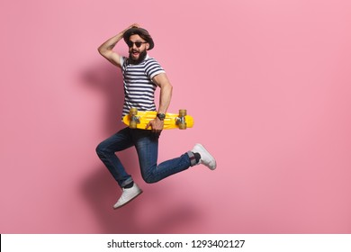 Handsome male in stylish outfit holding yellow skateboard and leaping on pink background