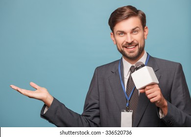 Handsome male tv journalist is reporting. He is speaking into the microphone and smiling. The man is pointing his right hand sideways. Isolated and copy space in left side