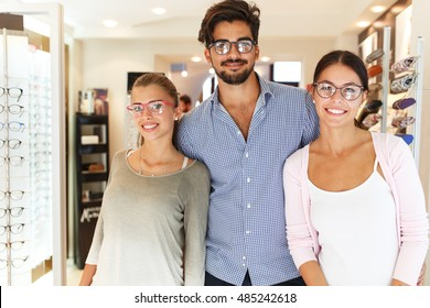 Handsome male and two beautiful females wearing eyeglasses in optician store.