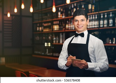 Handsome male waiter in cafe