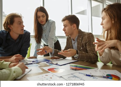 Handsome male worker in smart suit talking and sharing new interesting idea while colleagues listening to him. Creative youth coworking and planning project in office. Concept of conference.